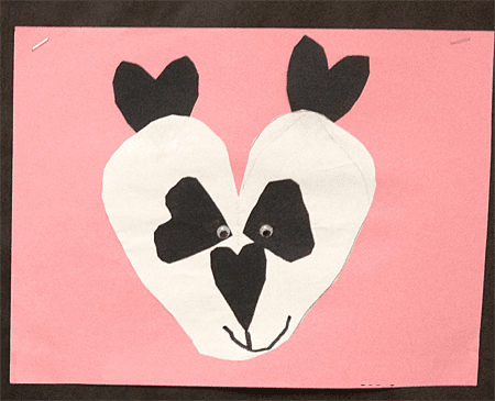 Paper panda head made from heart shapes mounted on pink paper