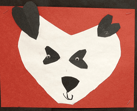 Paper panda head made from heart shapes mounted on red paper